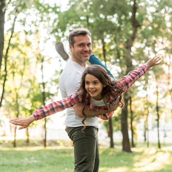 笑みを浮かべて男が公園で彼のかわいい娘を運ぶ