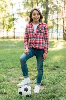 Девушка с футбольным мячом стоит на траве в парке