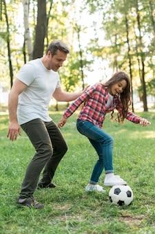 Отец и дочь играют в футбольный мяч в парке