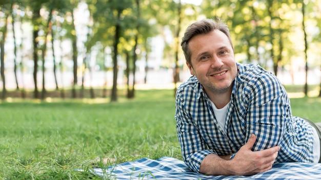 笑みを浮かべて男が公園で毛布の上に横たわるカメラを見て