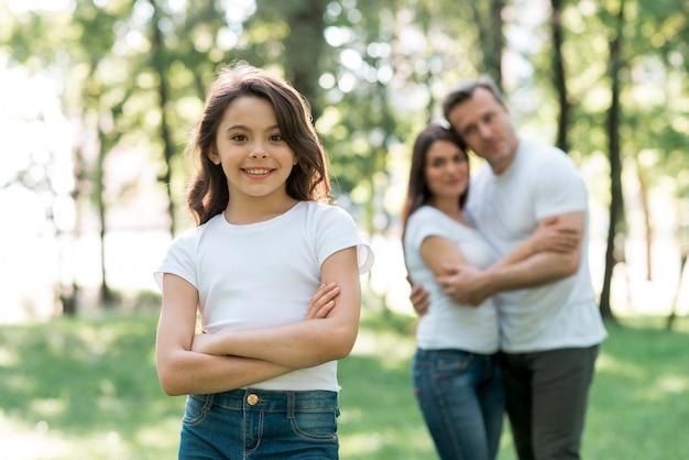 公園でカメラを見て彼らのかわいい娘の後ろに抱いてカップル