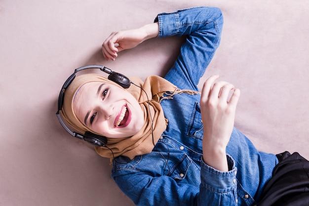 Мусульманская женщина слушает музыку в наушниках