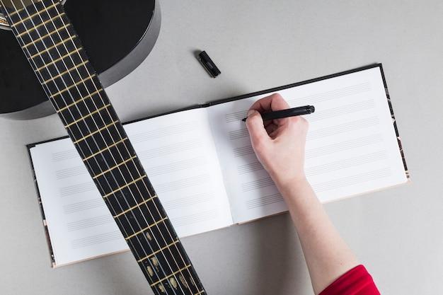 メモを書き留めてギターを持つ女性