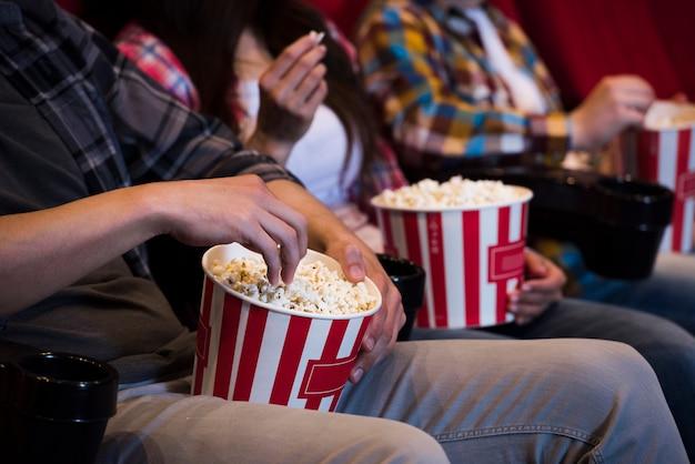 映画館でポップコーンを持つ人々