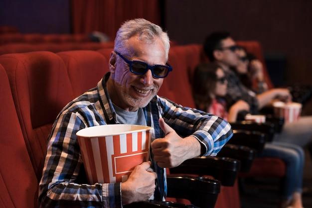 映画館で映画を見ている男