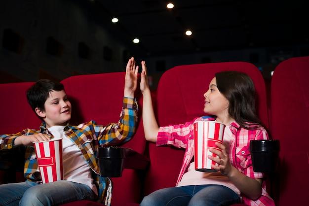 Мальчик и девочка смотрят фильм в кино