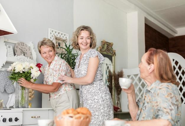 彼女の母親はコーヒーを飲んでいる間キッチンカウンターの上に花の花瓶を配置する娘と熟女
