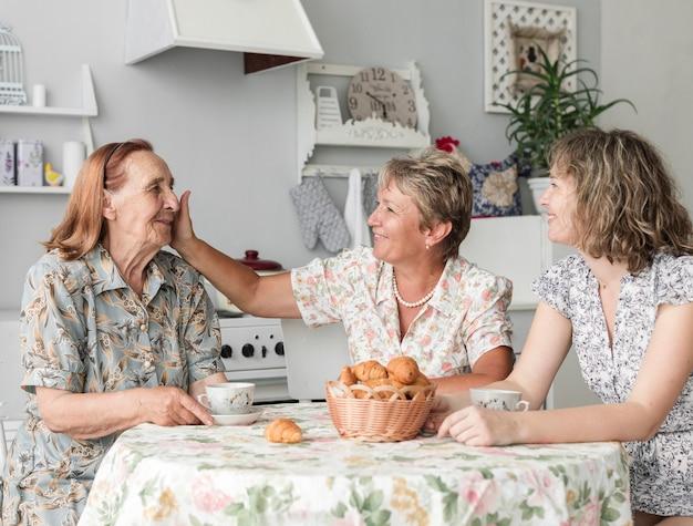中年の女性が朝食をとりながら彼女の年配の母親をなでる
