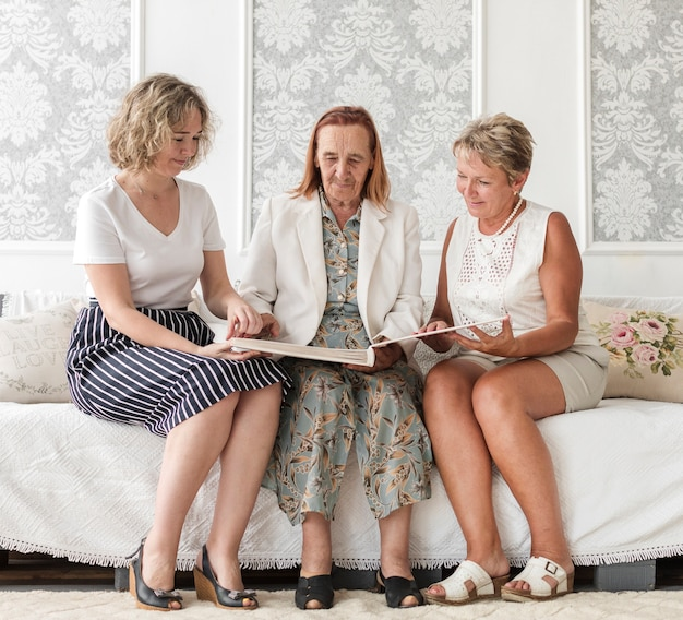 多世代女性のソファーに座っていると古い思い出のアルバムを探して