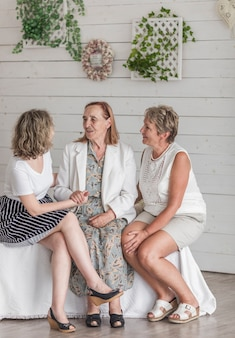 彼女の娘と自宅で壮大な娘が付いているソファーに座っていた年配の女性