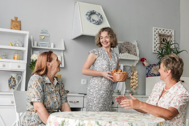 祖母と母クロワッサンの枝編み細工品バスケットを持って笑顔の娘を見て