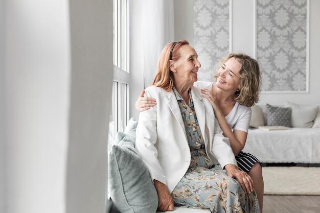Улыбается женщина, сидя на подоконнике с бабушкой у себя дома