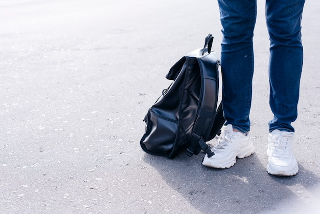 Низкая часть человека, стоящего на улице с черным рюкзаком