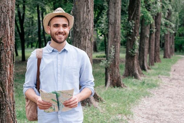公園で地図を持って帽子をかぶっている若い男の笑みを浮かべてください。