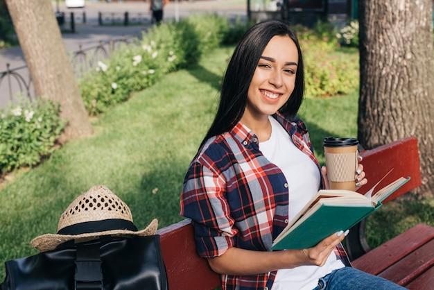 公園のベンチに座りながら本と使い捨てのコーヒーカップを保持している女性の笑みを浮かべてください。