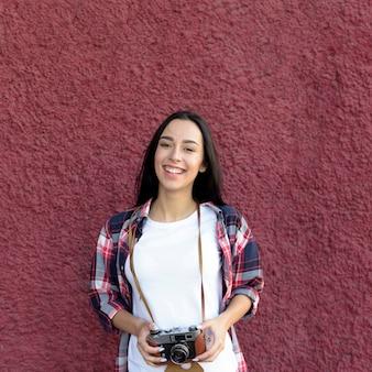 Портрет улыбающейся женщины, держащей камеру, стоящую против темно-коричневой стены