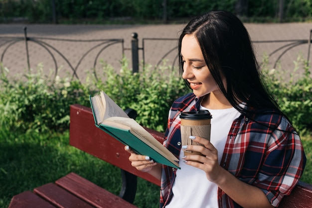 Усмехаясь книга чтения молодой женщины с держать устранимую кофейную чашку пока сидящ на стенде на парке