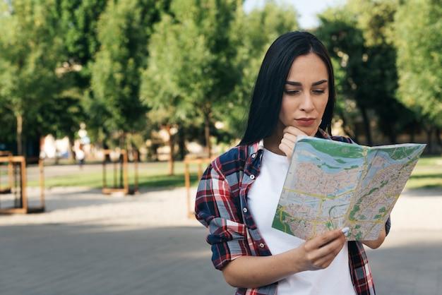 Молодая женщина смотрит на карту и думает в парке