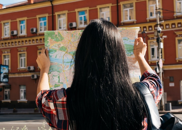 赤い建物外観の背景を持つマップを読む女性の背面図