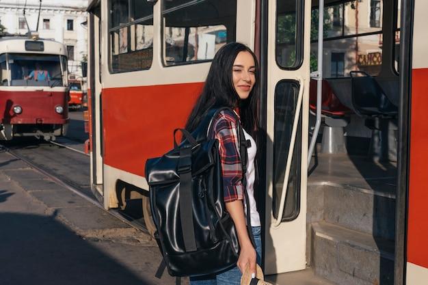 路上の路面電車の近くに立ってバックパックを運ぶ笑顔の女性