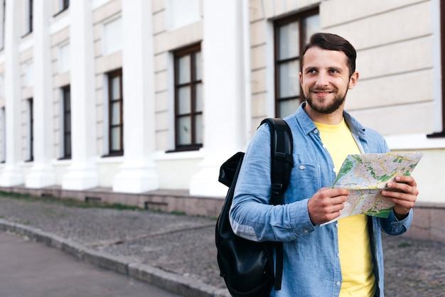 離れた通りに立っている探している地図を持って笑顔の旅行者男