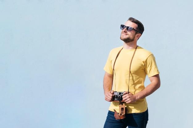 Улыбающийся человек в темных очках держит камеру и смотрит в сторону