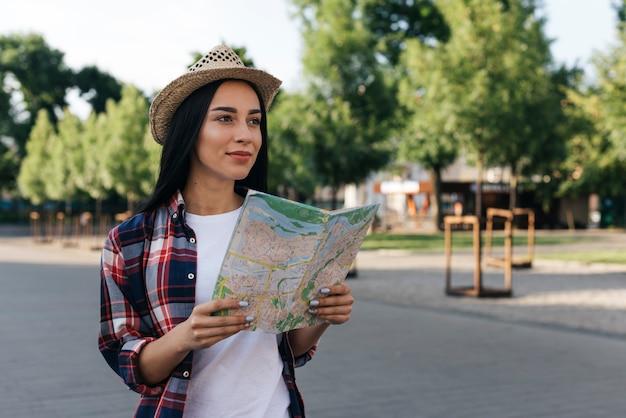 通りに地図を持って若い笑顔の女性を考えています。