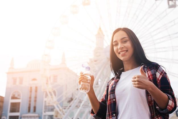幸せな若い女観覧車の前に立って、水のボトルを保持している間ジェスチャー親指を表示