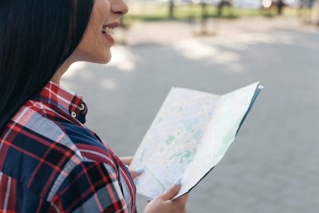 通りに立っているマップを保持している笑顔の女性のクローズアップ