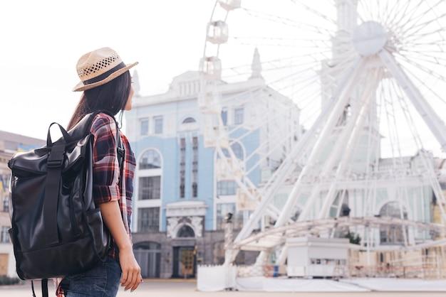 Вид сзади женщины, несущей рюкзак и смотрящей на колесо обозрения