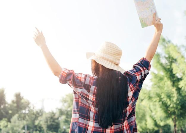Вид сзади женщина держит карту и поднял руку