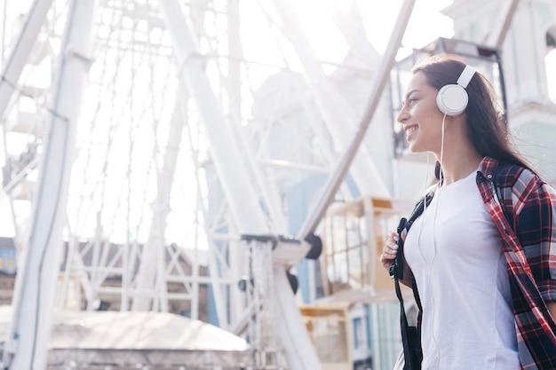 魅力的な若い女性は観覧車の近くに立っているヘッドフォンで音楽を聴く