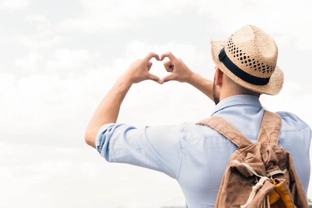 曇り空を背景に指からハート形を作る旅行者男の背面図
