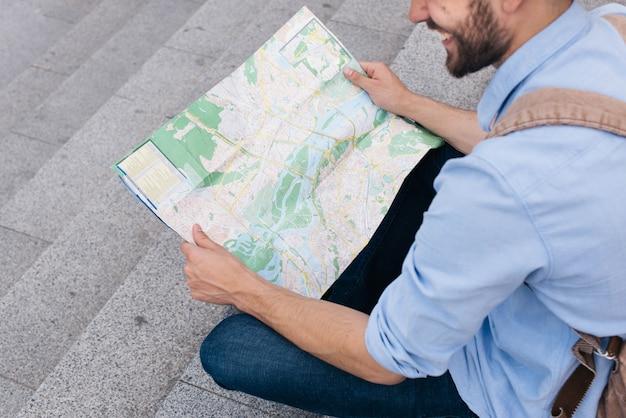 階段の上に座って地図を読んでいる笑みを浮かべて男の高角度のビュー