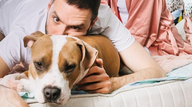 ベッドの中で犬を持つ男