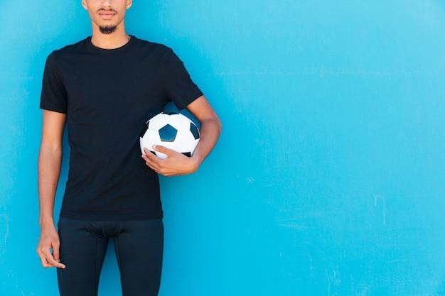 腕の下でサッカーボールを持つ民族のスポーツマンの作物
