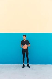 路上でバスケットボールを持つ民族の選手