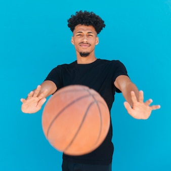 民族の若い男がカメラにバスケットボールを投げる