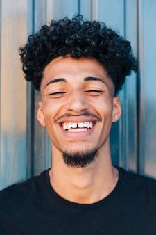 巻き毛を持つ陽気な黒の若い男