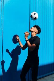 Тренировка мыжского спортсмена с футбольным мячом против голубой стены