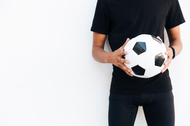 Молодой черный человек в черном с футбольным мячом