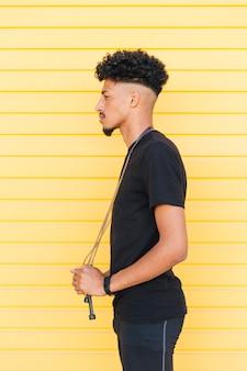 Молодой стильный черный человек со скакалкой