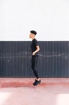 Многорасовый спортивный молодой человек, прыжки через скакалку