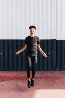 Веселый этнический спортивный парень прыгает через скакалку