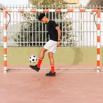 Черный спортсмен пинает футбол на стадионе
