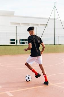 Черный спортсмен играет в футбол на спортивной площадке