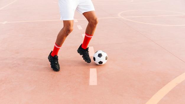 Черный человек играет в футбол на стадионе