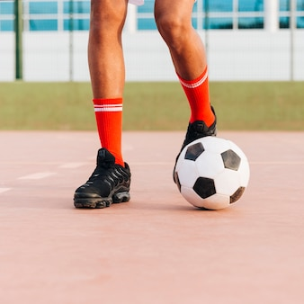 スタジアムでサッカーをしてスポーツマンの足