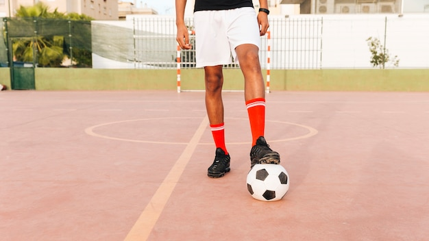 晴れた日にスタジアムでサッカーのフットボール選手の足