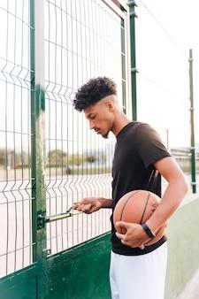 民族の若い男がバスケットボールのコートを開く